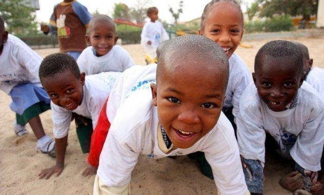 Diversi bambini sorridono mentre giocano e vengono inquadrati dalla telecamera.