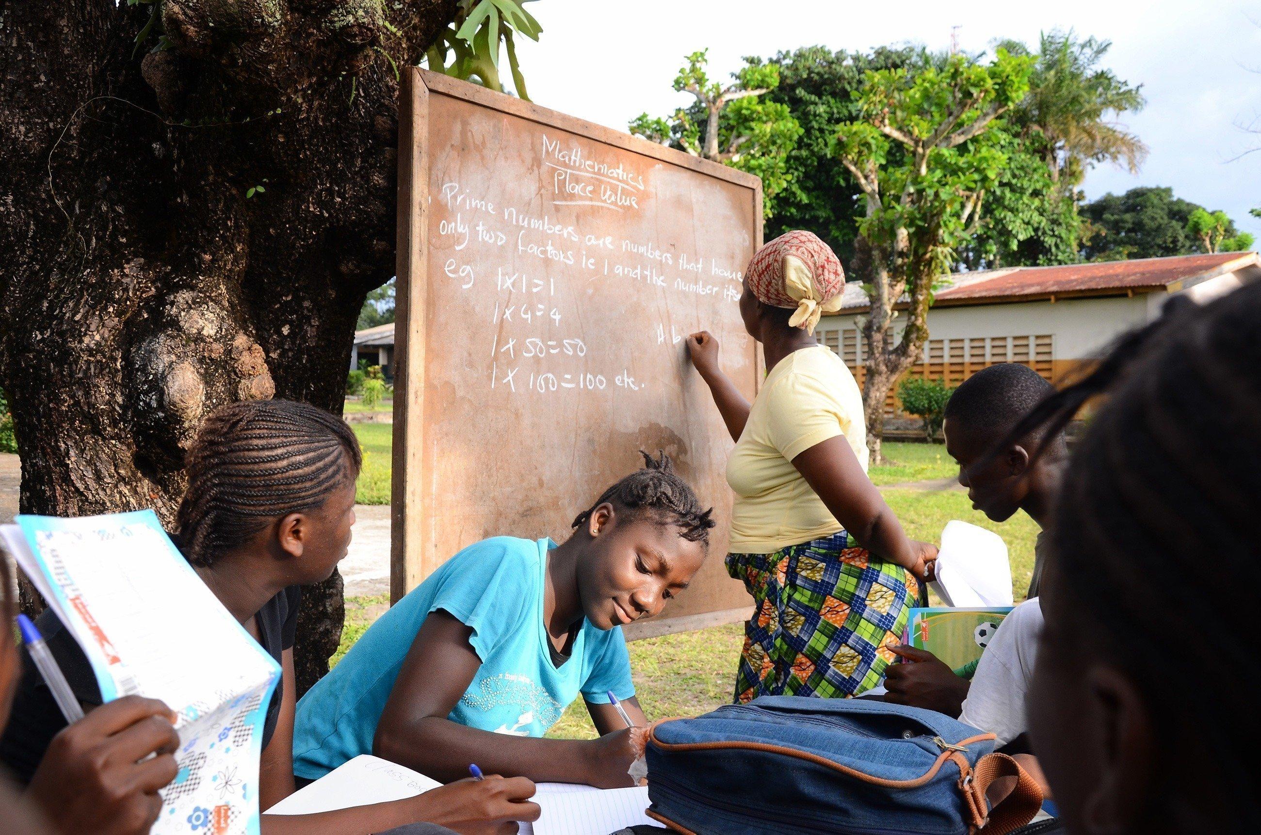 Bambini che studiano con una lavagnetta.