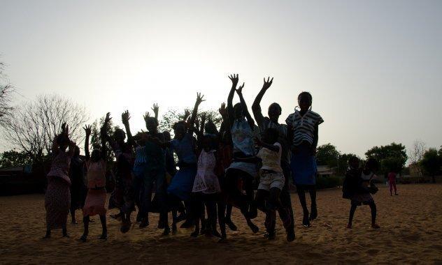 Una classe di bambini africani di SOS Villaggi dei Bambini salta ed esulta.