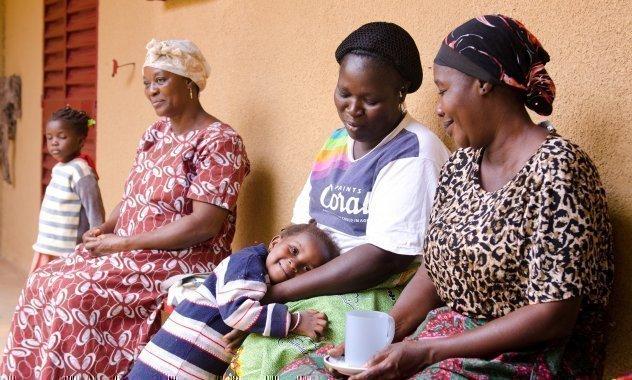 Tre mamme africane SOS Villaggi dei Bambini sedute su una panchina di fronte a una casa. Una mamma abbraccia il suo bambino.