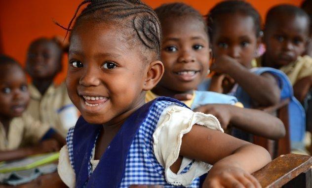 Bambini africani di SOS Villaggi dei Bambini a scuola durante la pausa pranzo.