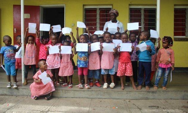 Una classe di bambini africani di SOS Villaggi dei Bambini mostra fieramente le proprie pagelle.