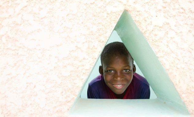 Un ragazzino guarda fuori da una finestra di forma triangolare.