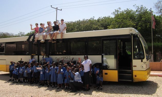 Una classe di bambini africani di SOS Villaggi dei Bambini in gita di fronte a un autobus.