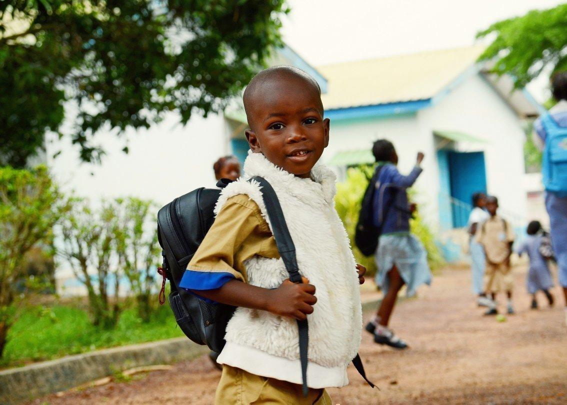 Bambino africano con zaino andando a scuola.