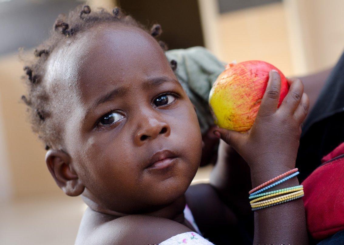 Bambina africana con in mano una mela.
