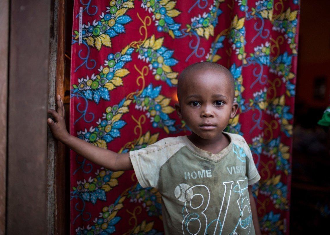 Un bambino piccolo che guarda nell'obiettivo davanti a un tappeto colorato.