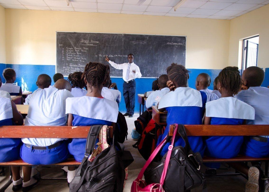 Alcuni bambini in uniforme seduti sui banchi di scuola che ascoltano il loro insegnante.