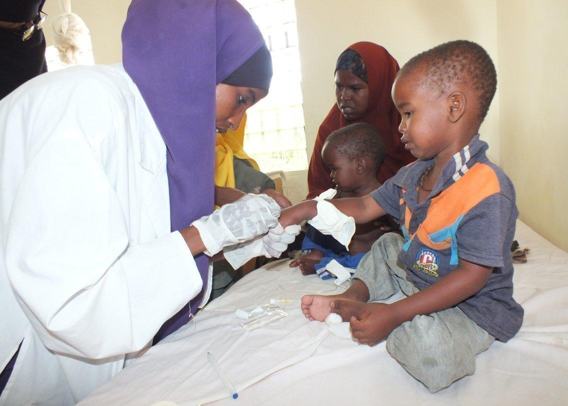 Una donna fa una puntura a un bambino.