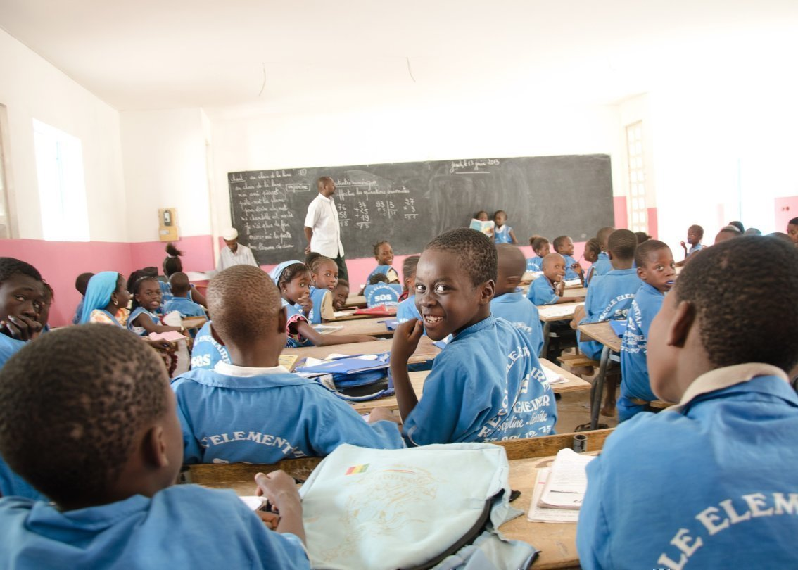 Uno dei molti alunni a scuola si volta indietro ridendo.