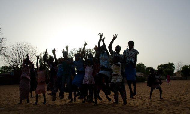 Un gruppo di bambini salta in alto sullo sfondo del tramonto.