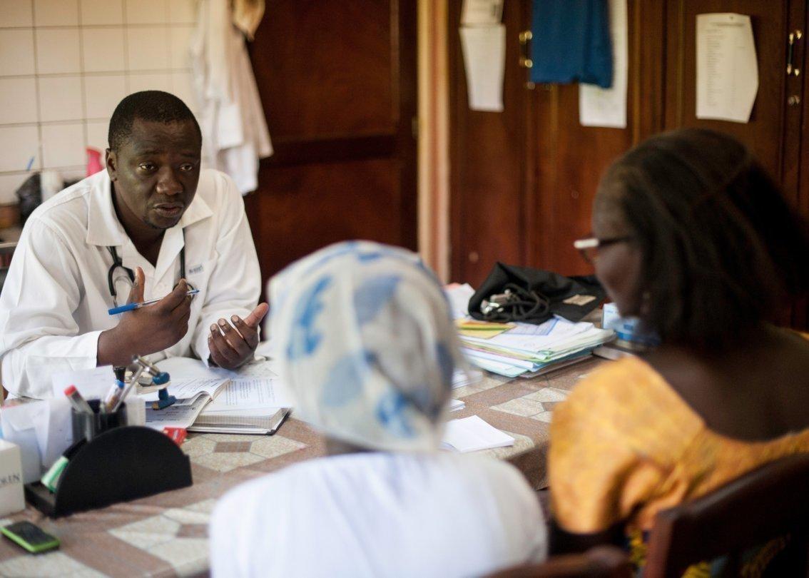 Un medico africano è intento a spiegare qualcosa a due donne.