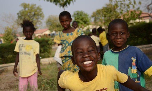 Molti bambini ridono guardando nell'obiettivo.