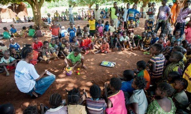 Molti bambini siedono in cerchio con un collaboratore SOS e guardano un bambino al centro.