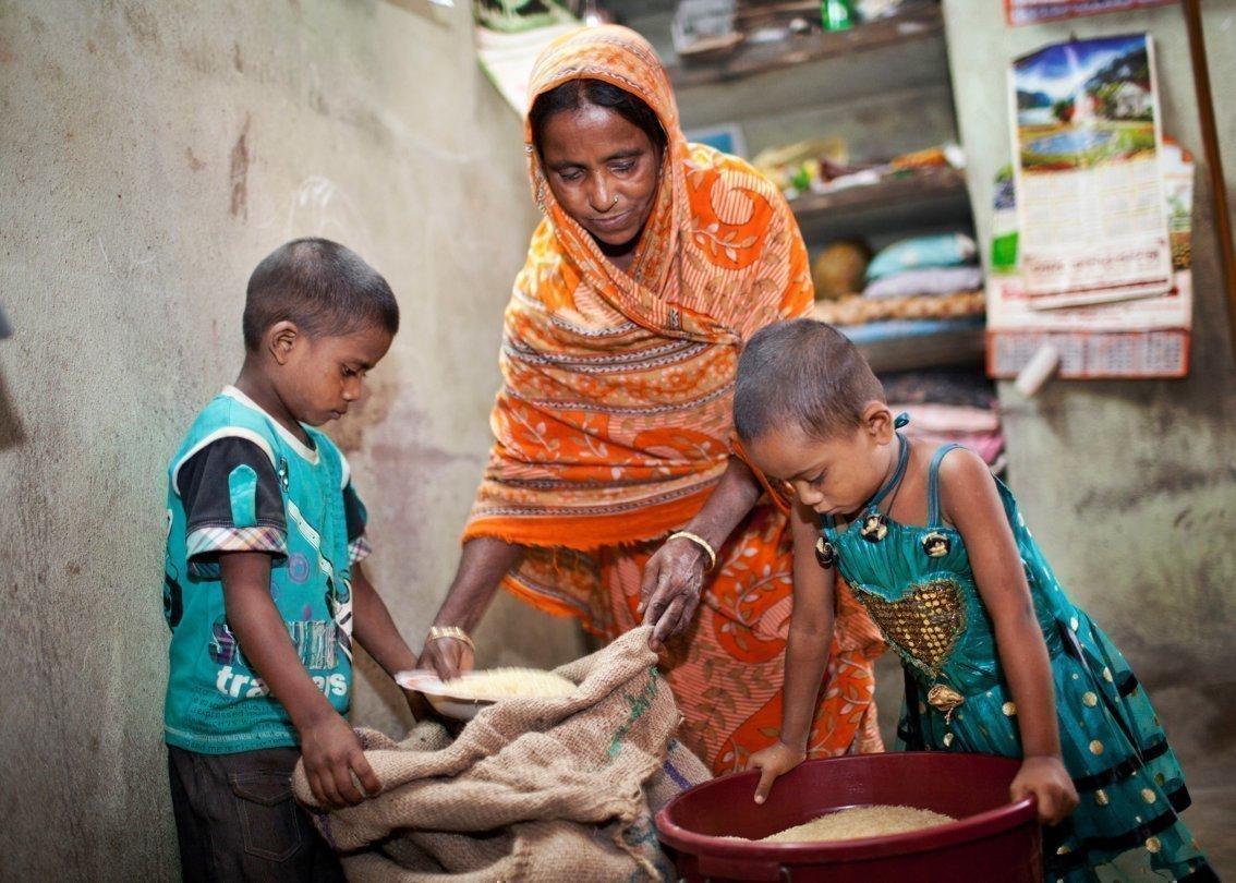 Due bambini guardano all'interno di sacchi e contenitori pieni di chicchi.