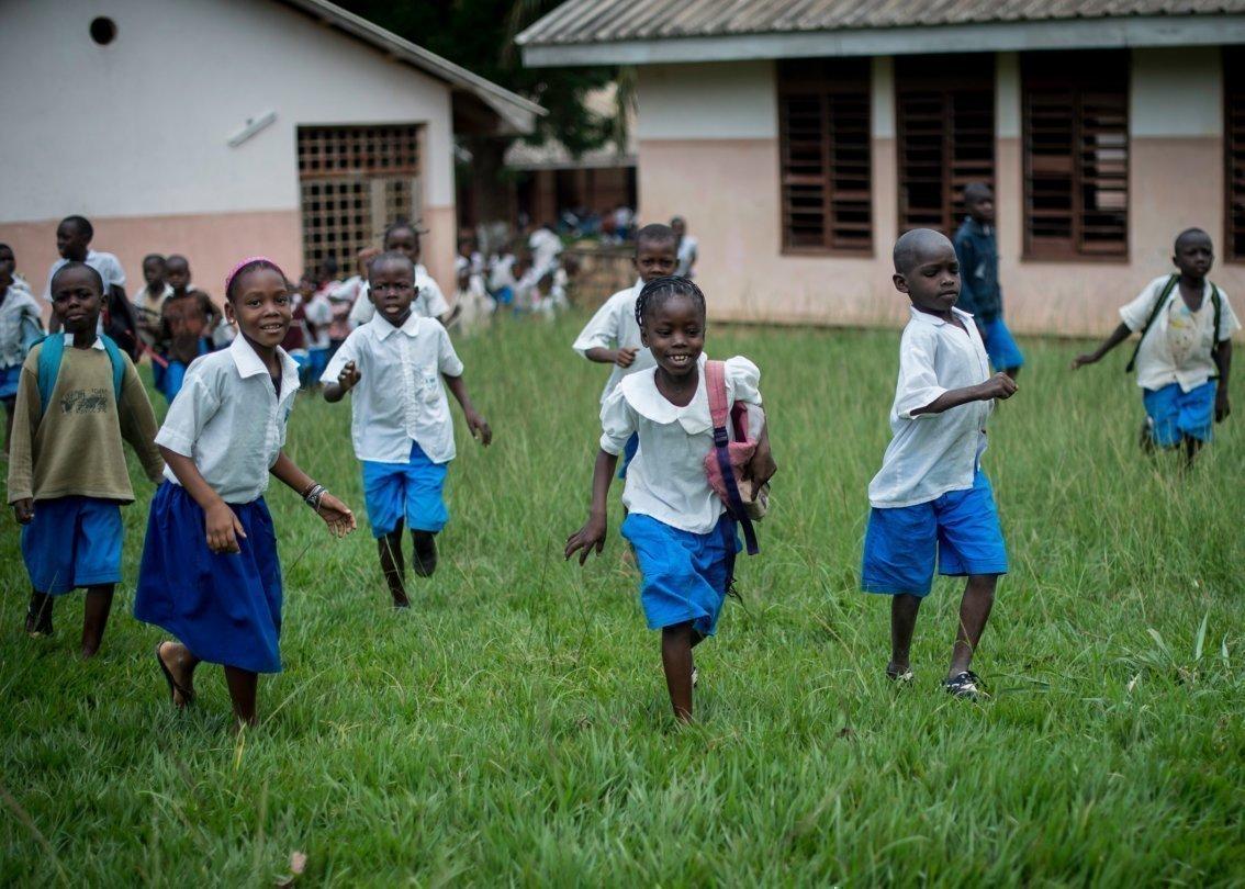 Bambini escono correndo dalla scuola al termine delle lezioni.
