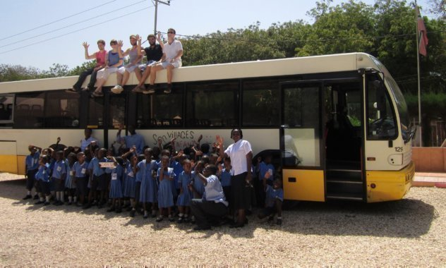 Una classe in piedi davanti a un pullman in cui siedono alcuni collaboratori SOS.