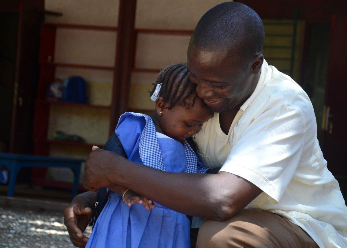 Un padre SOS abbraccia calorosamente una bambina.