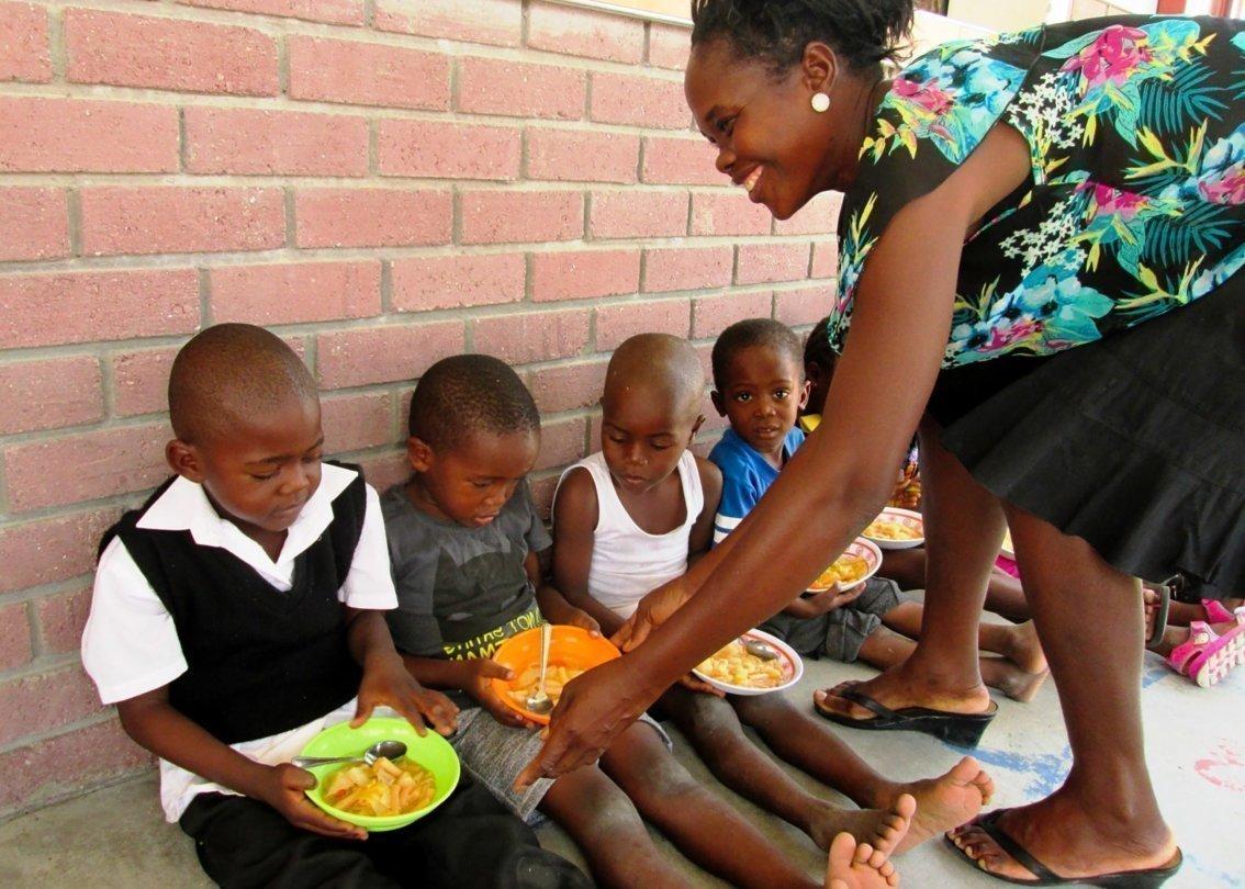 Una madre SOS dà da mangiare ai bambini.