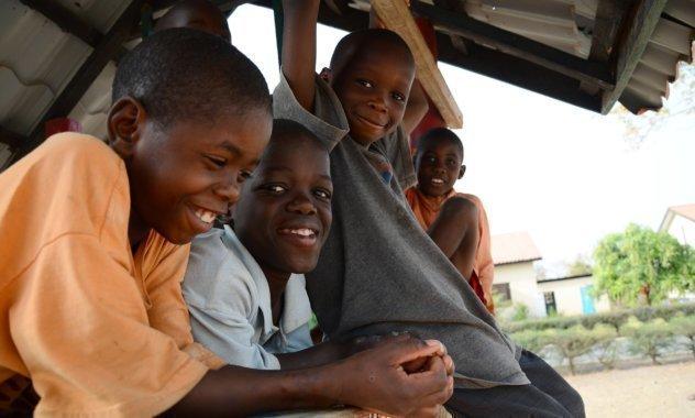 Alcuni bambini siedono sotto un tetto provvisorio.