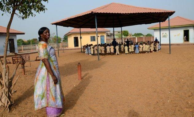 Una donna indiana in piedi davanti a un gazebo nel quale sta avendo luogo un evento della scuola.