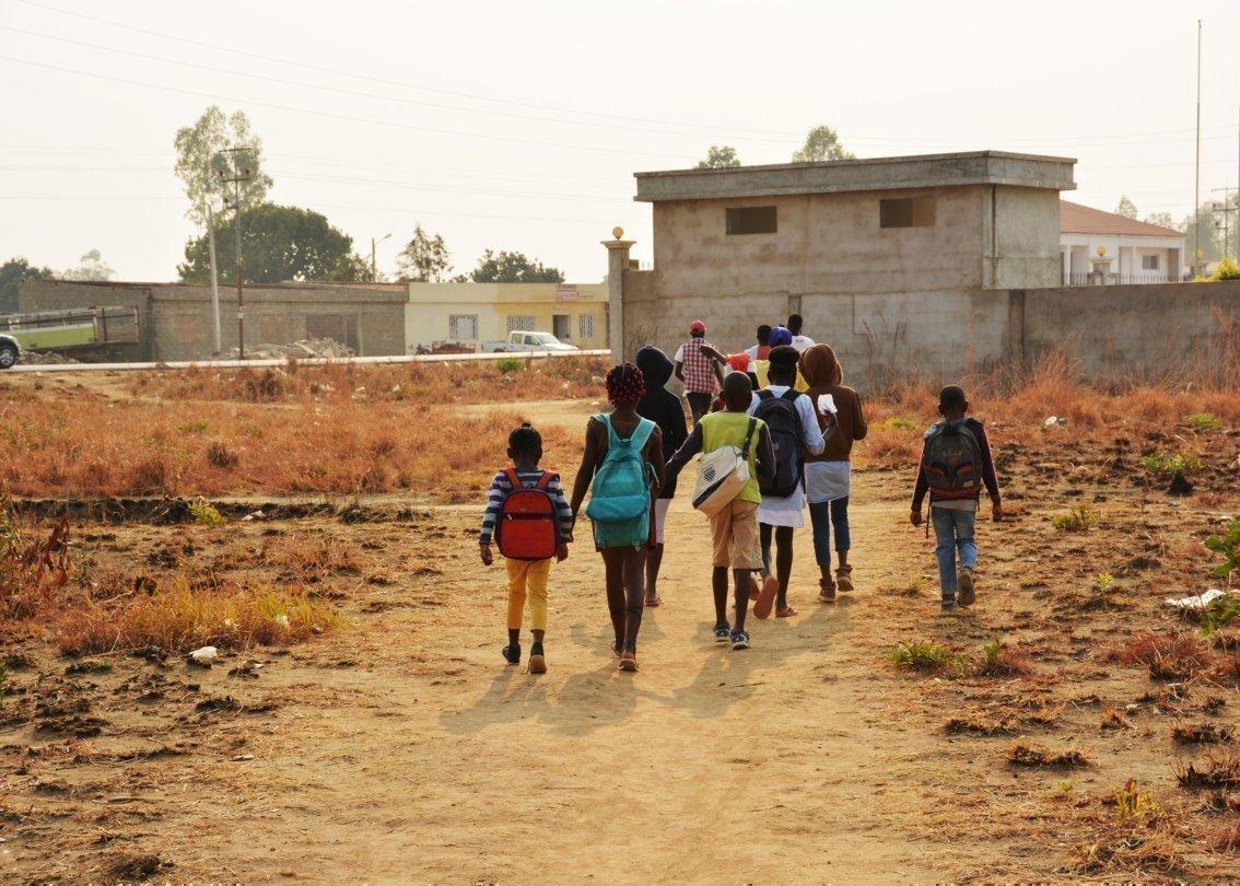 Alcuni bambini con zaino in spalla che si stanno dirigendo verso l'edificio scolastico.