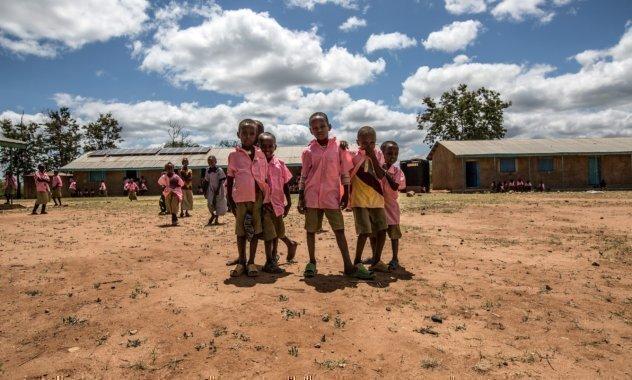 Alunni in camicia rosa davanti alla loro scuola.