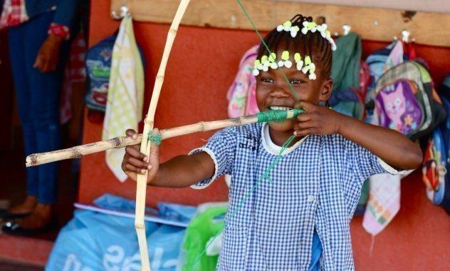 Bambina gioca con arco e freccia in legno.